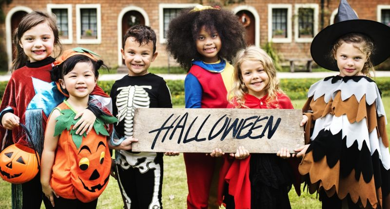 Kids holding Halloween sign in their costumes